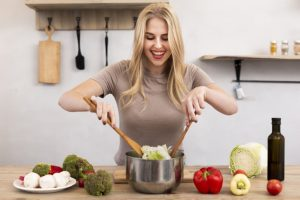 happy woman mixing bowl with salad